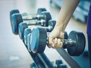 Woman hand lifting dumbbell in gymnasium with fitness equipments in backgroound