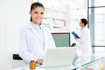 Smiling Asian female pharmacist working in pharmacy