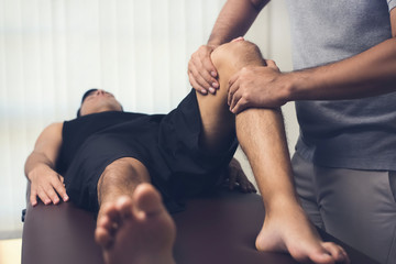 Physiotherapist treating athlete male patient