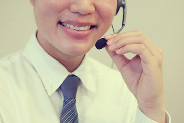 close up asian call center employee man smiling with service-mind,vintage tone color filter