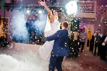 Newly married couple dancing on their wedding party with heavy smoke and multicolored lights on the background.