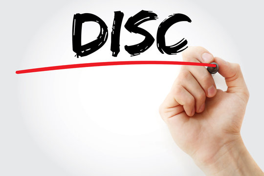 Hand writing DISC (Dominance, Influence, Steadiness, Conscientiousness acronym - personal assessment tool to improve work productivity) with marker, concept background