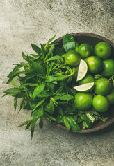Flatlay of freshly picked organic limes and mint leaves for making cocktail or lemonade in wooden plate over grey concrete stone background, top view, vertical composition