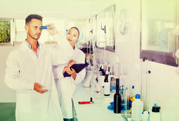 Two researchers in white coat checking wine acidity in laboratory