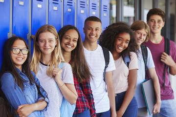 Teenage school kids smiling to camera in school corridor Wall mural