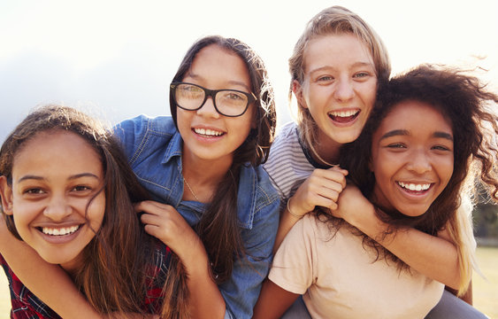 Four teenage girls having fun piggybacking outdoors