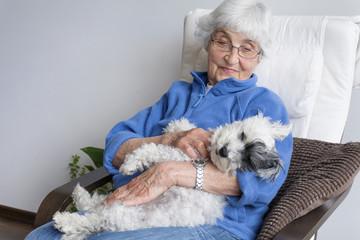 smiling senior woman hugging her poodle dog at home