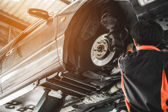 Car lifted in automobile service for fixing. Mechanic male in garage automobile checking