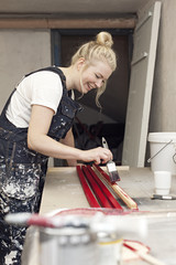 Smiling woman paints in her craft studio