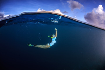 Freediver girl under water line in deep blue ocean against cloudy sky background