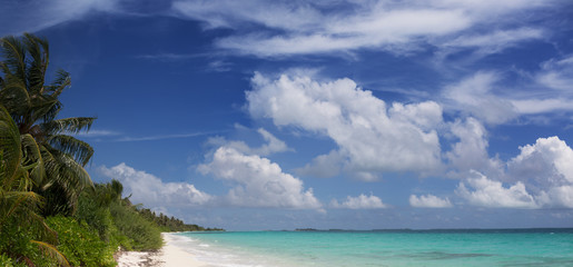 Panoramic view of Maldivian tropical beach with bright sea water under blue sky and white clouds on background