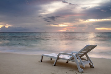 Sunbed with nobody under tropical sunset sky