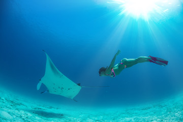 Model freediver with fins in tropical water watching manta ray underwater on blue background