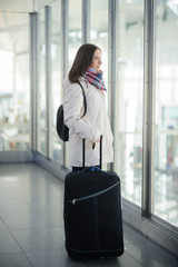 The young woman with a suitcase at the airport.