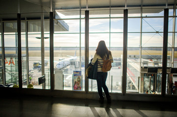 A woman with a backpack standing at the large window in the airport.