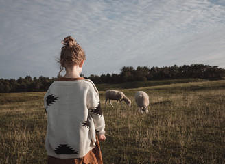 a little girl in the field with sheep