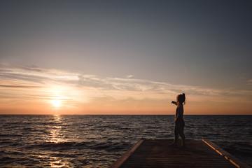 Kleines Mädchen auf Steg am Meer bei Sonnenuntergang