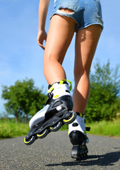 Female legs in inline skates in action outdoors on sunny day. Fun time activity.