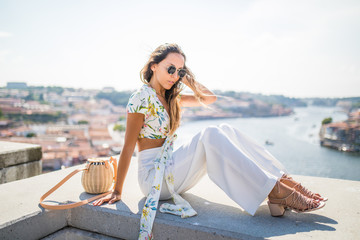 Young woman sitting on ledge watching the city of Porto from above, Portugal