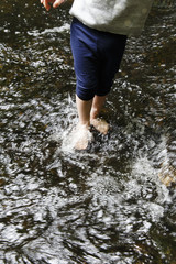 USA, Maine. Legs and feet from a toddler who is standing in a shallow stream.