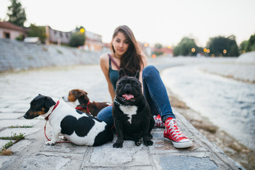 Dog walker with dogs enjoying outdoors next to city river.