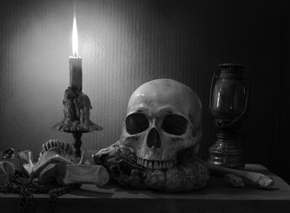 Still Life of skull and bone with fetters and candle on the wooden plank in dim light night