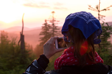 A young girl takes photos of nature on the phone