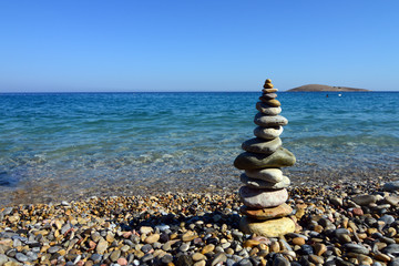 stack of  balanced stones near sea shore, refreshing blue waves summer, beach at the sunset time in Mugla, Turkey