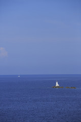 Lighthouse on rocks, Photo of white lighthouse on rocks with blue sea and sailing boat in the background