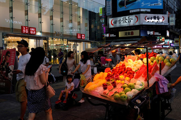 Tourists walk near food stalls and casual clothing store Uniqlo at Ximending shopping district