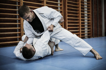 Two young males practicing judo together.