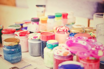 Arts and Crafts: Paintbrush with multiple colored jars. Creative hobby