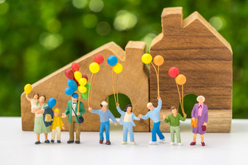 Miniature people with happy family holding balloons with wooden house as property or mortgage concept