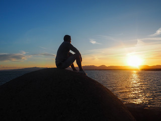 A man is watching the sunset on the coast