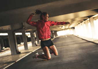 Young female runner jumps around,expressing positive emotion.She made her goal of the day.