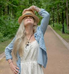 Cute woman in light white dress and wearing a straw hat posing on camera in park outdoors against green background. Long white hair.