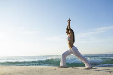 Woman doing warrior yoga pose on the beach, Bali, Indonesia