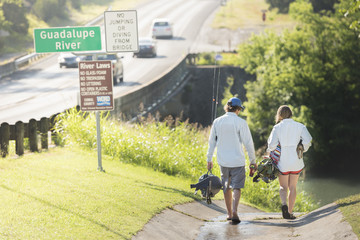 A Man And Woman With Their Dog Walking Toward The Guadalupe River For Fly Fishing