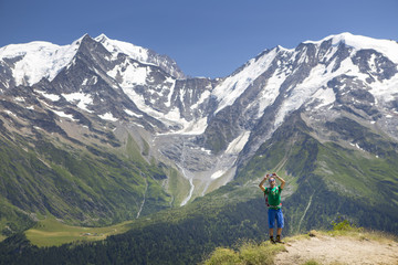 A male hiker is taking a picture with his smart phone on the summit of Mont Joly. Mont Blanc is in the background.
