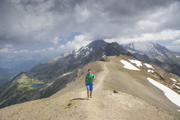 A solo male hiker is walking on the ridge of the Tete des Fours with Mont Blanc in the distance.