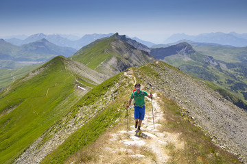 A solo male hiker on a mountain ridge near Mont Joly in France, halfway the Tour du Mont Blanc.