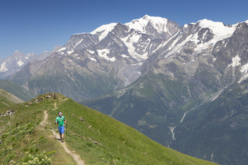 A hiker on the summit ridge of Mont Joly, a mountain on the Tour du Mont Blanc.
