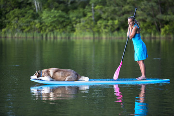 A young woman stand up paddle boards with her Siberian husky.