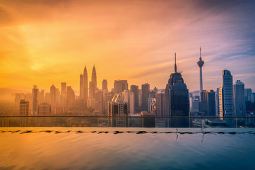 Photo Stands Kuala Lumpur Cityscape of Kuala lumpur city skyline with swimming pool on the roof top of hotel at sunrise in Malaysia.