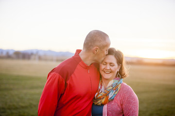 A man kisses his smiling wife on the head, while standing in a field at sunset.