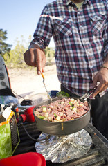 A camper cooking breakfast on the tailgate of his truck.