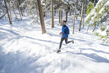Man running on trail covered in snow
