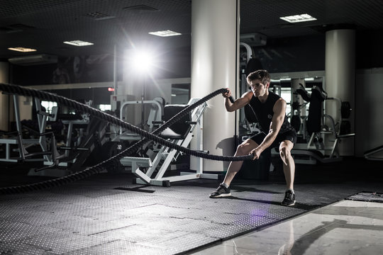 Crossfit battling ropes at gym workout exercise. Crossfit