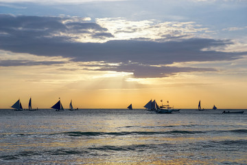 Horizon with sailing and catamaran silhouette over the sea at sunset
