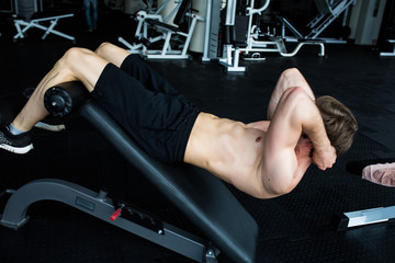 Muscular man exercising doing sit up exercise.